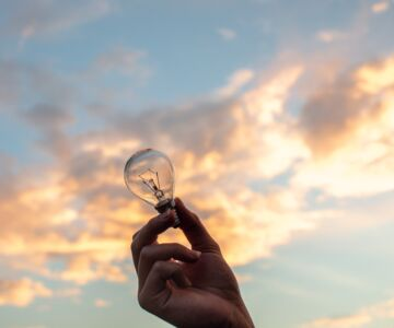 person holding clear light bulb 1314410 1